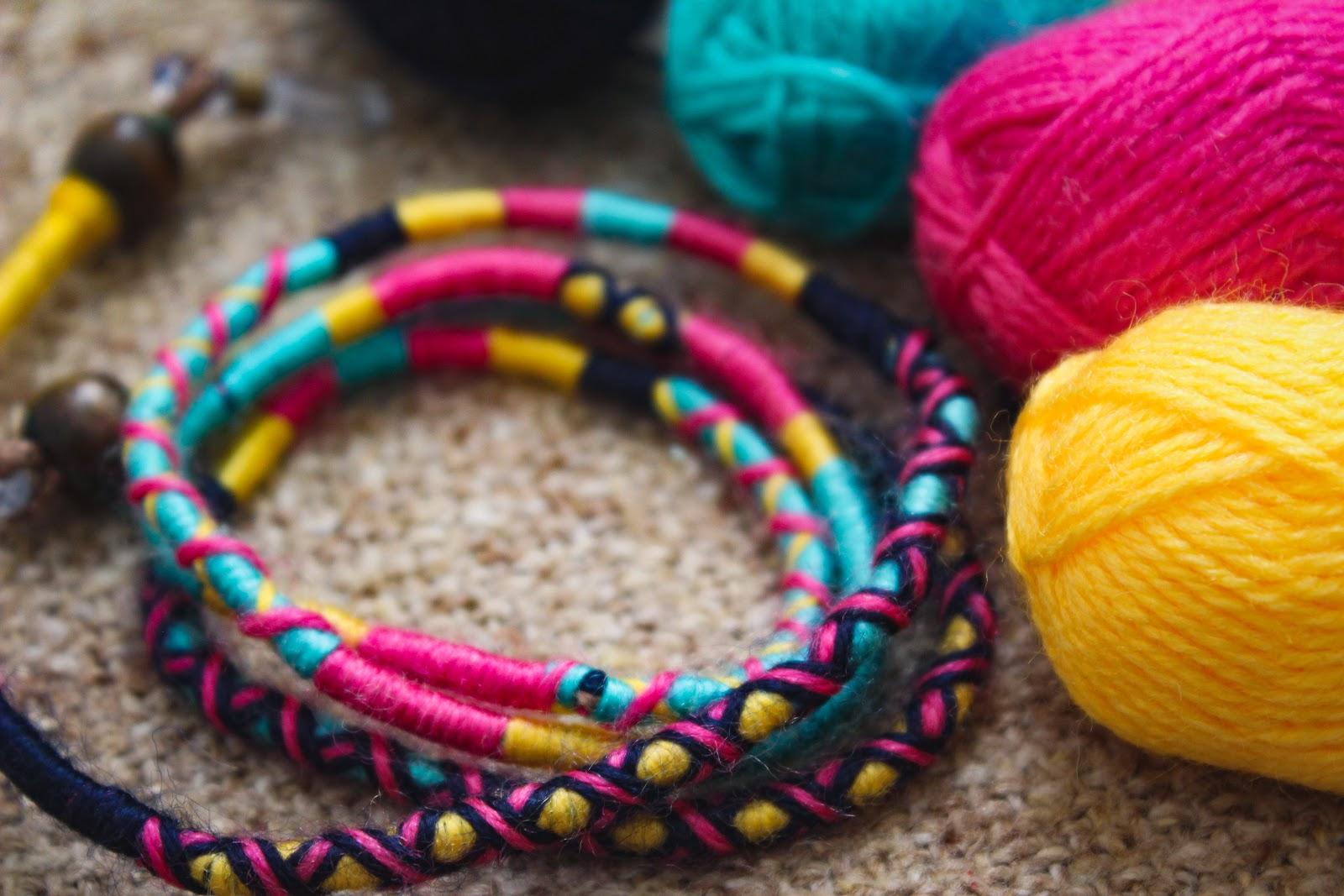 balls of yarn around a piece of jewelry handmade with yarn