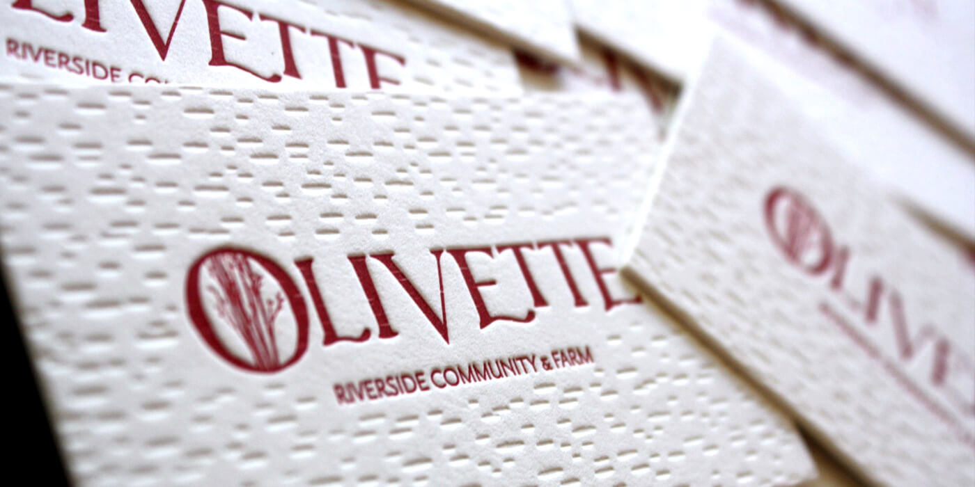Olivette Riverside Community business card detail shows letter-pressed offwhite cards with deep imprint of birch bark texture and red spot-print logo.