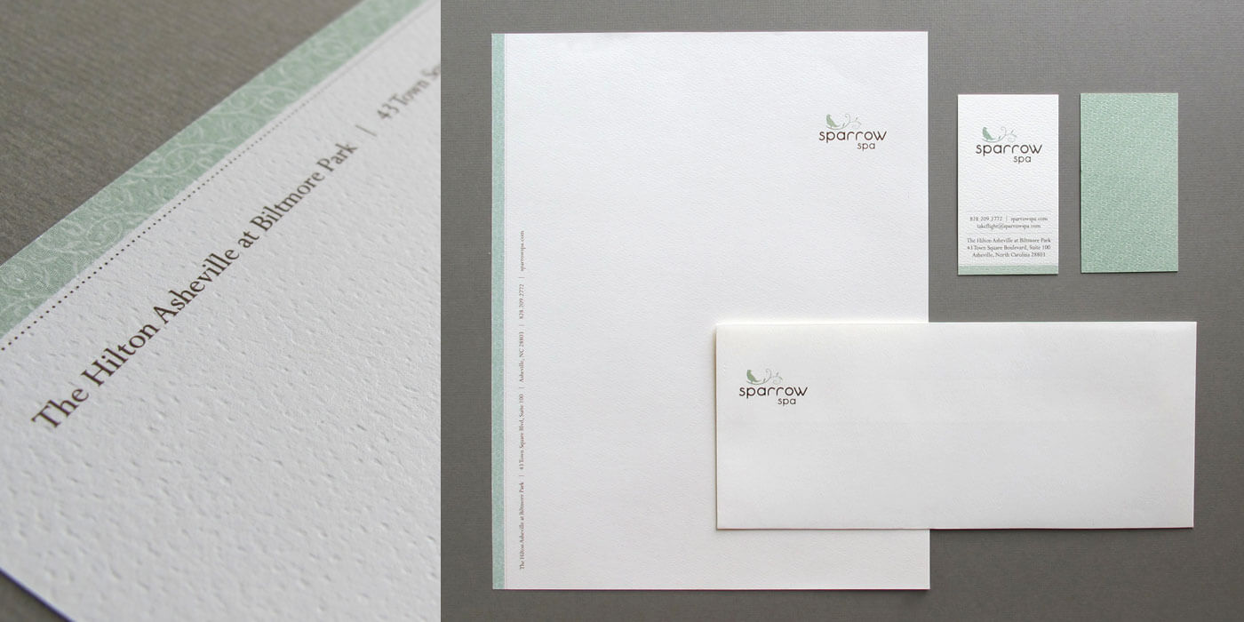 Sparrow Spa stationery items arranged on a table. Includes letterhead, business card, and envelopes printed on a textured paper.