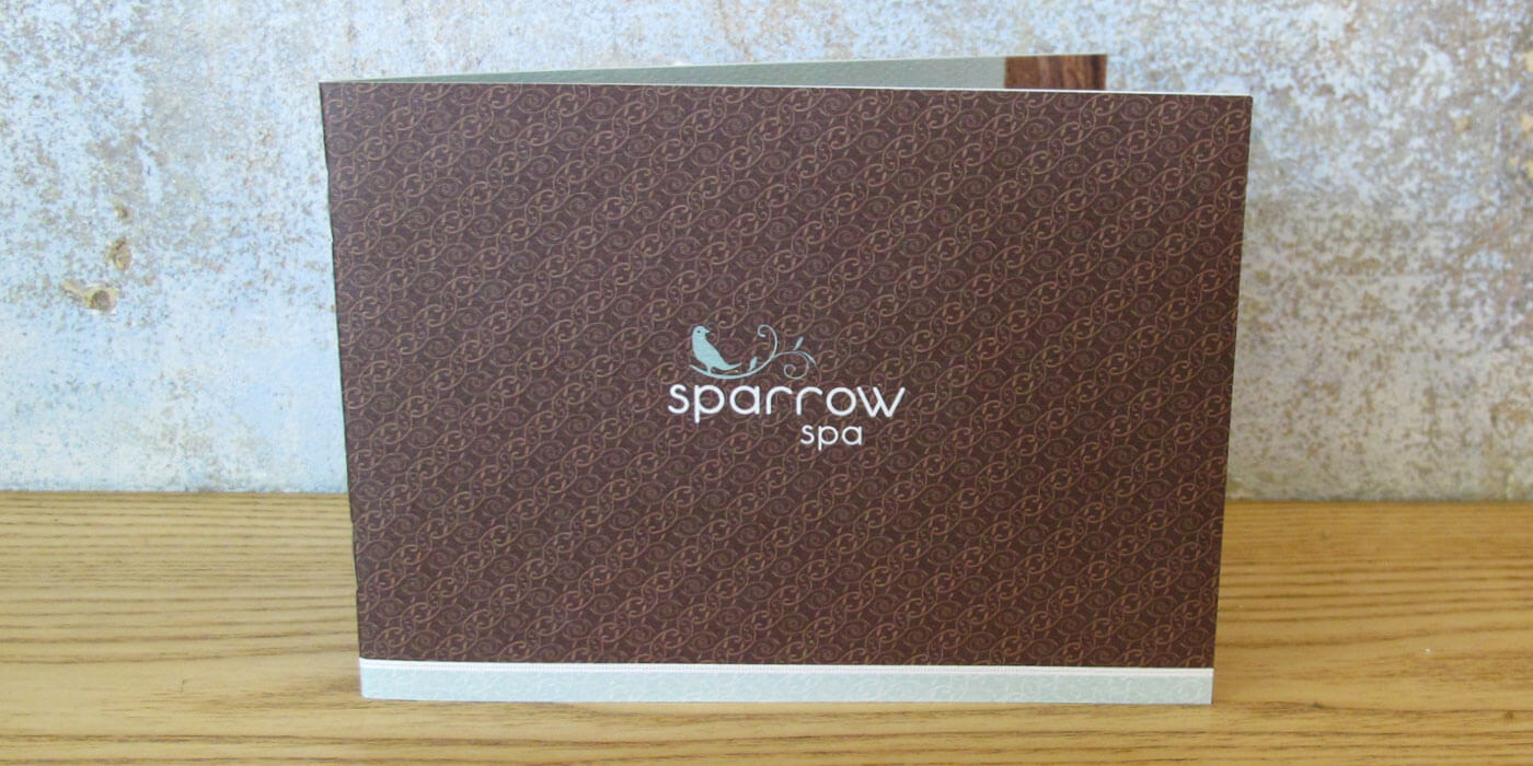Sparrow Spa menu of services cover with small sparrow logo surrounded by a brown branch patterned background.