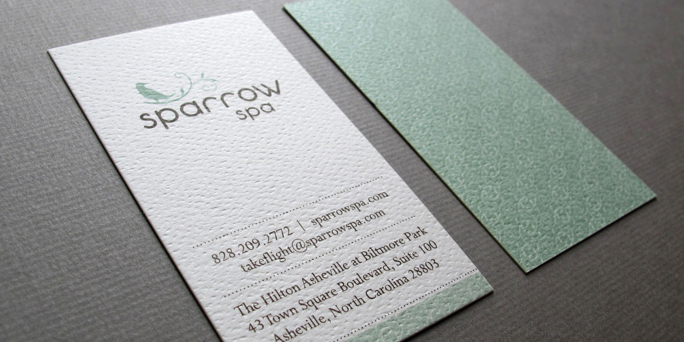 Sparrow Spa vertical business cards has information on a white textures front and a branch patter in light blue on the back