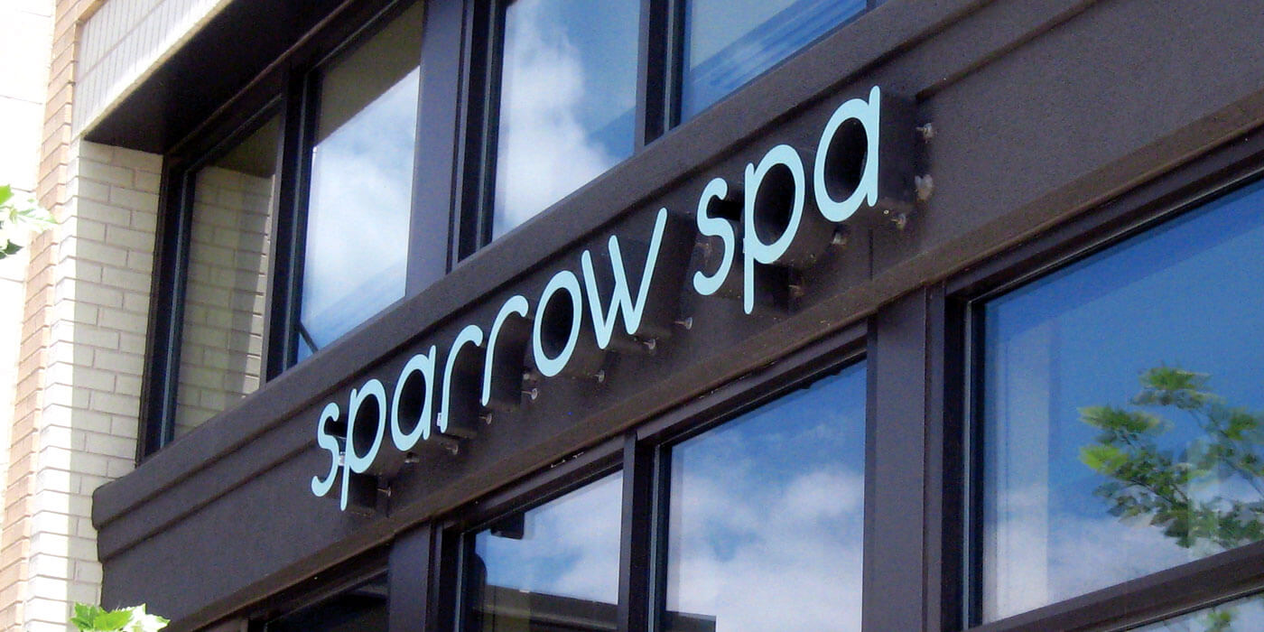 Sparrow Spa exterior sign with extruded pale blue text. Blue cloudy sky reflection in windows.