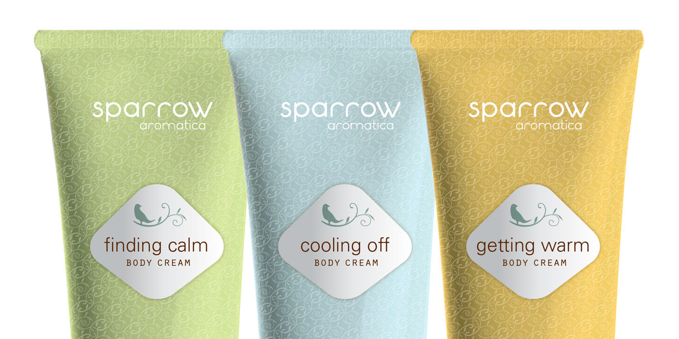 Pastel green, blue and orange lotion bottles for Sparrow Spa shown against a white background