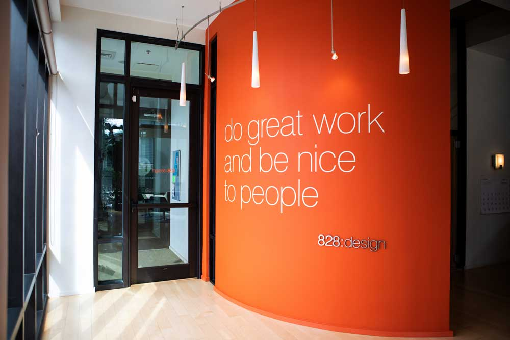 "828:design studio entry curved orange wall with motto ""do great work and be nice to people"" in large white letters."