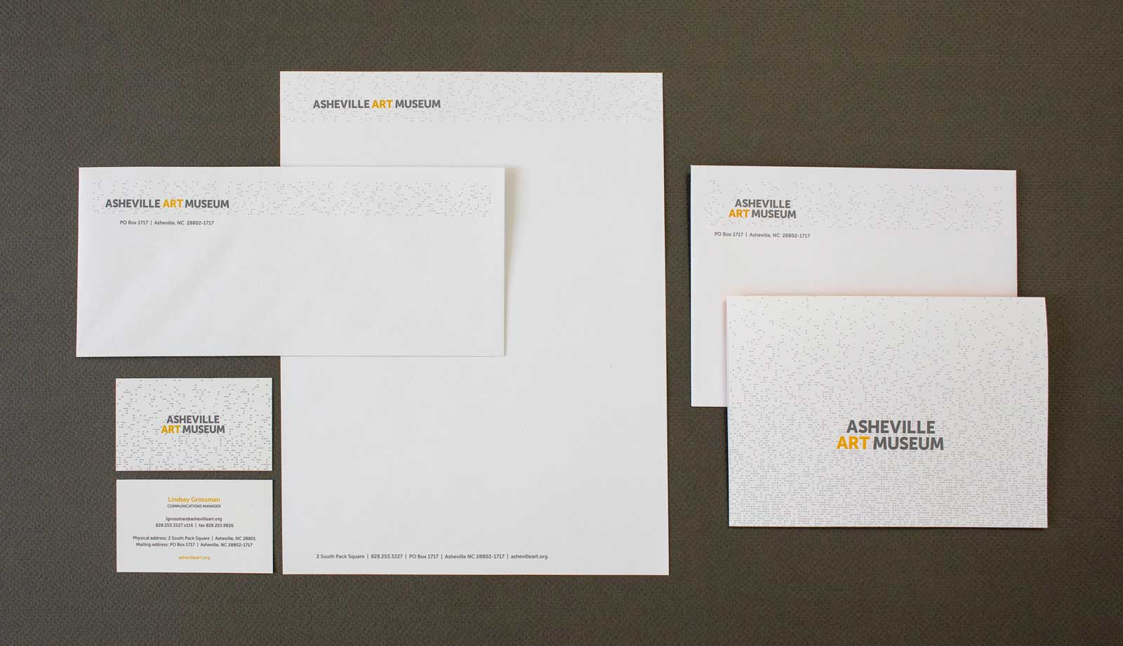 Asheville Art Museum stationery set that includes letterhead, business card, envelope, and notecard and notecard envelope. Design on white paper with logo and perforated pattern.