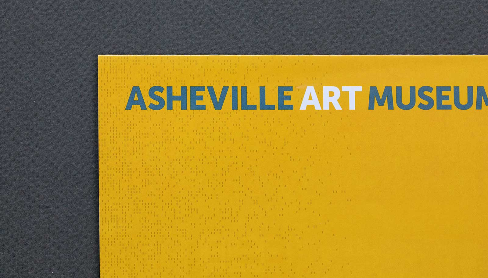 Tightly cropped view of New Membership brochure for the Asheville Art Museum shows close-up of vertical logo and perf pattern on gold background.