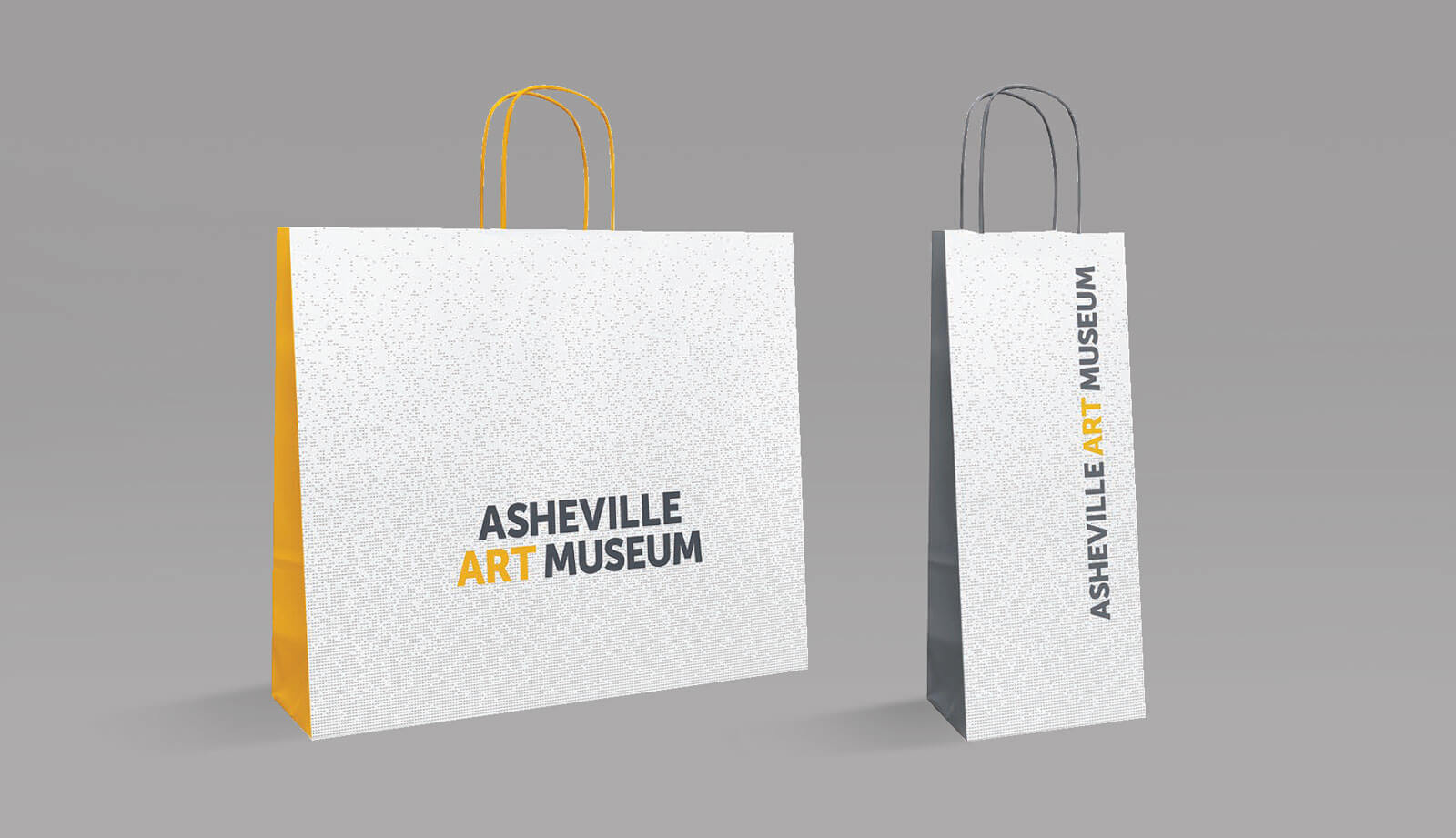 Asheville Art Museum retail bag mockups. Horizontal and vertical bags with gold and gray side panels. Logo centered and vertically oriented on a perforated pattern background.