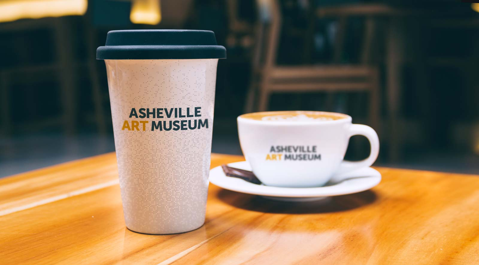 White ceramic coffee cup with rubber lid and coffee mug show with Asheville Art Museum logo centered on a perforated background pattern.