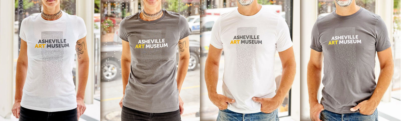 Male and female models wearing Asheville Art Museum shirts in gray and white, featuring the AAM logo centered in a vertical strip of a perforated pattern.
