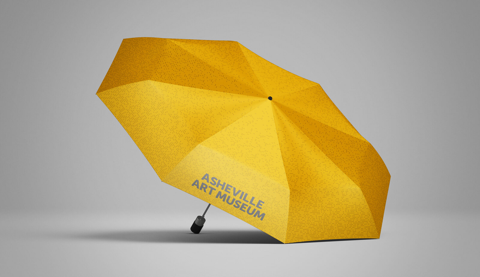 Side view mockup of a gold umbrella with perforated pattern and Asheville Art Museum logo