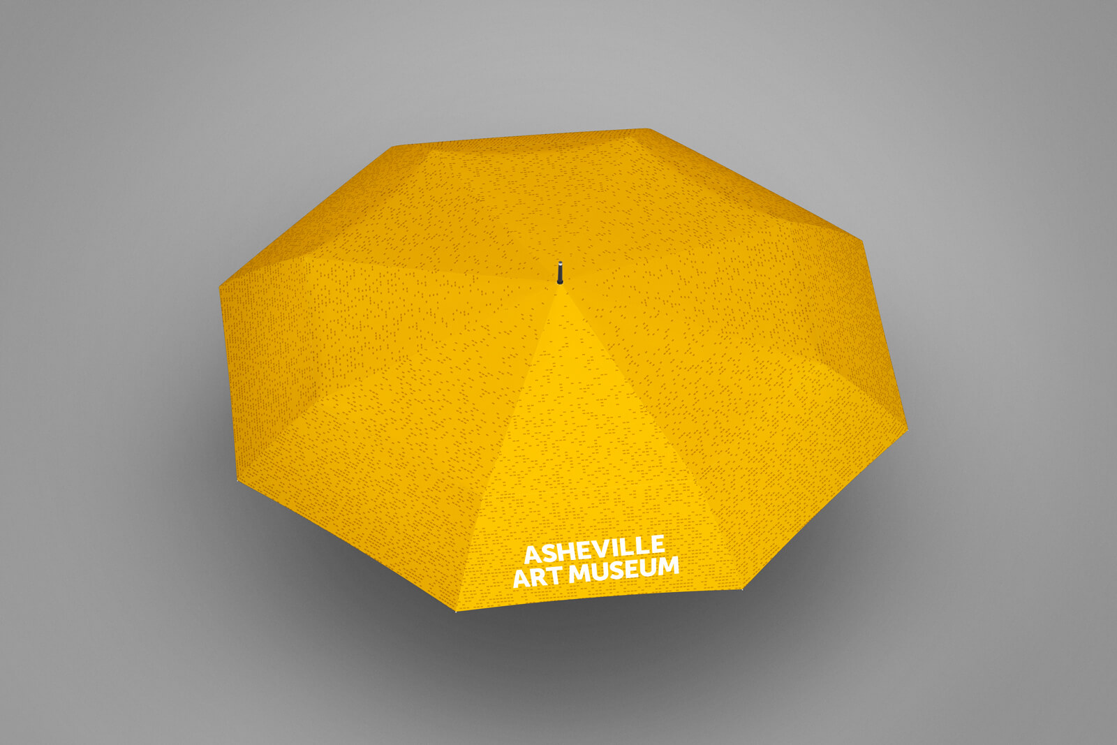 Top view mockup of a gold umbrella with perforated pattern and Asheville Art Museum logo