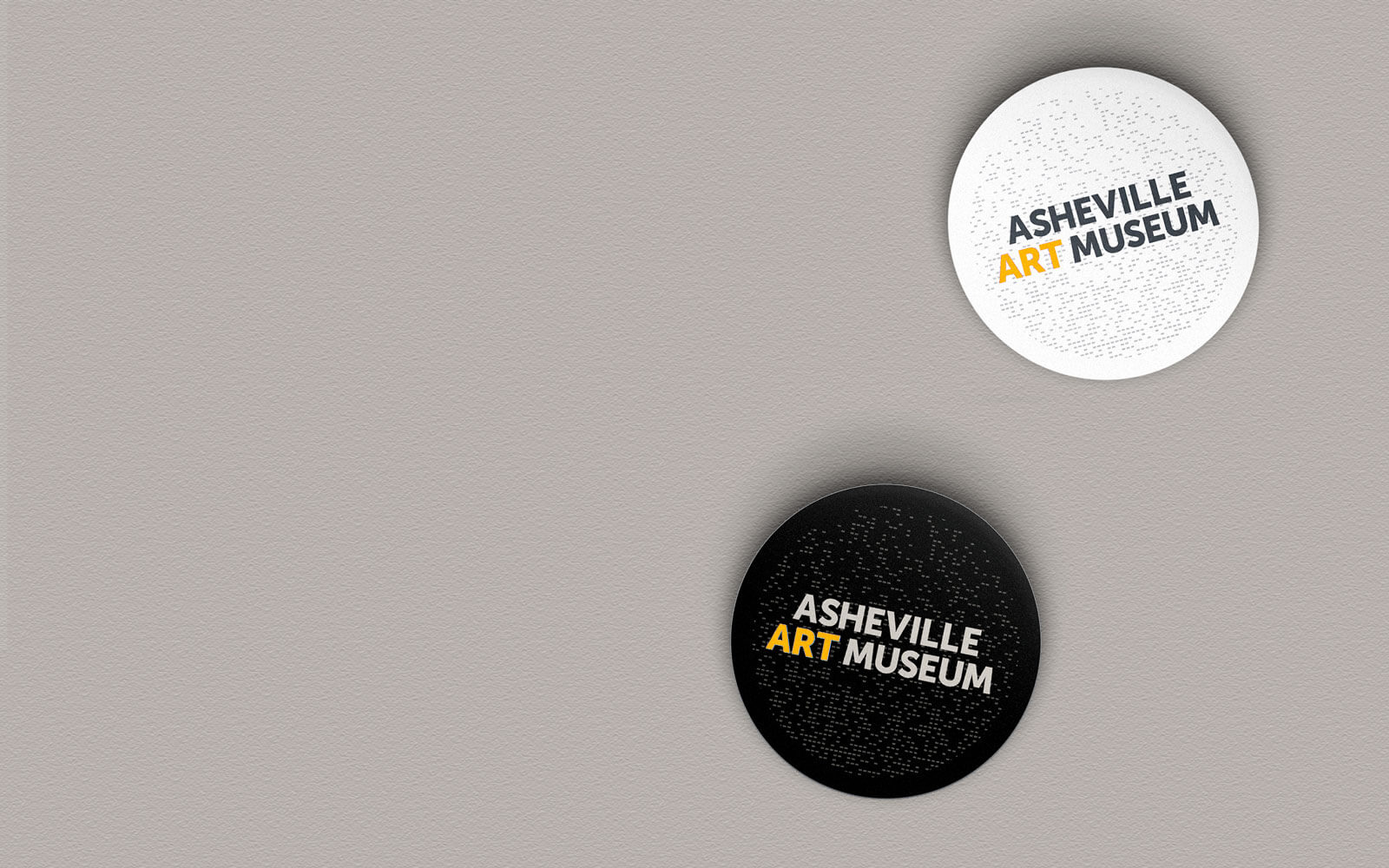 Mockup rendering of Asheville Art Museum buttons with stacked logo centered. One button is white and one button is black.