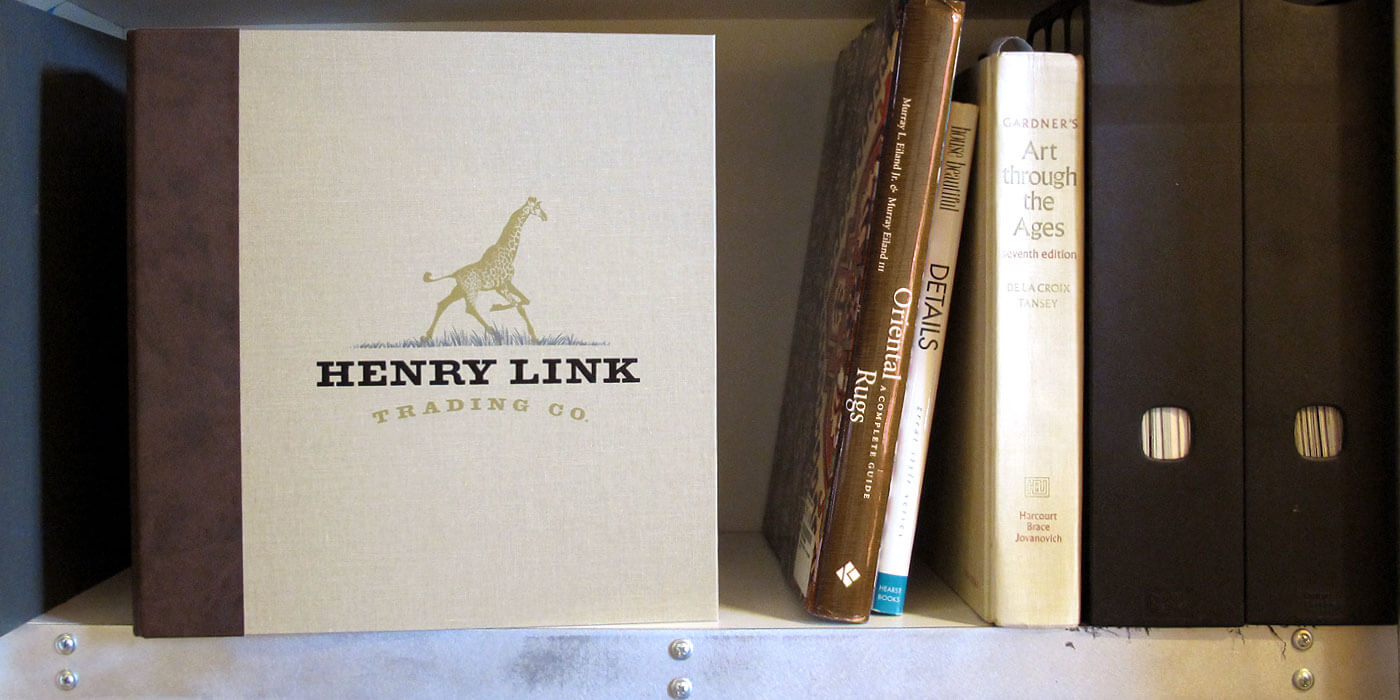 Lexington Furniture's Henry Link Trading Company natural canvas binder with giraffe logo. Binder is shown on a shelf with other art and design books.