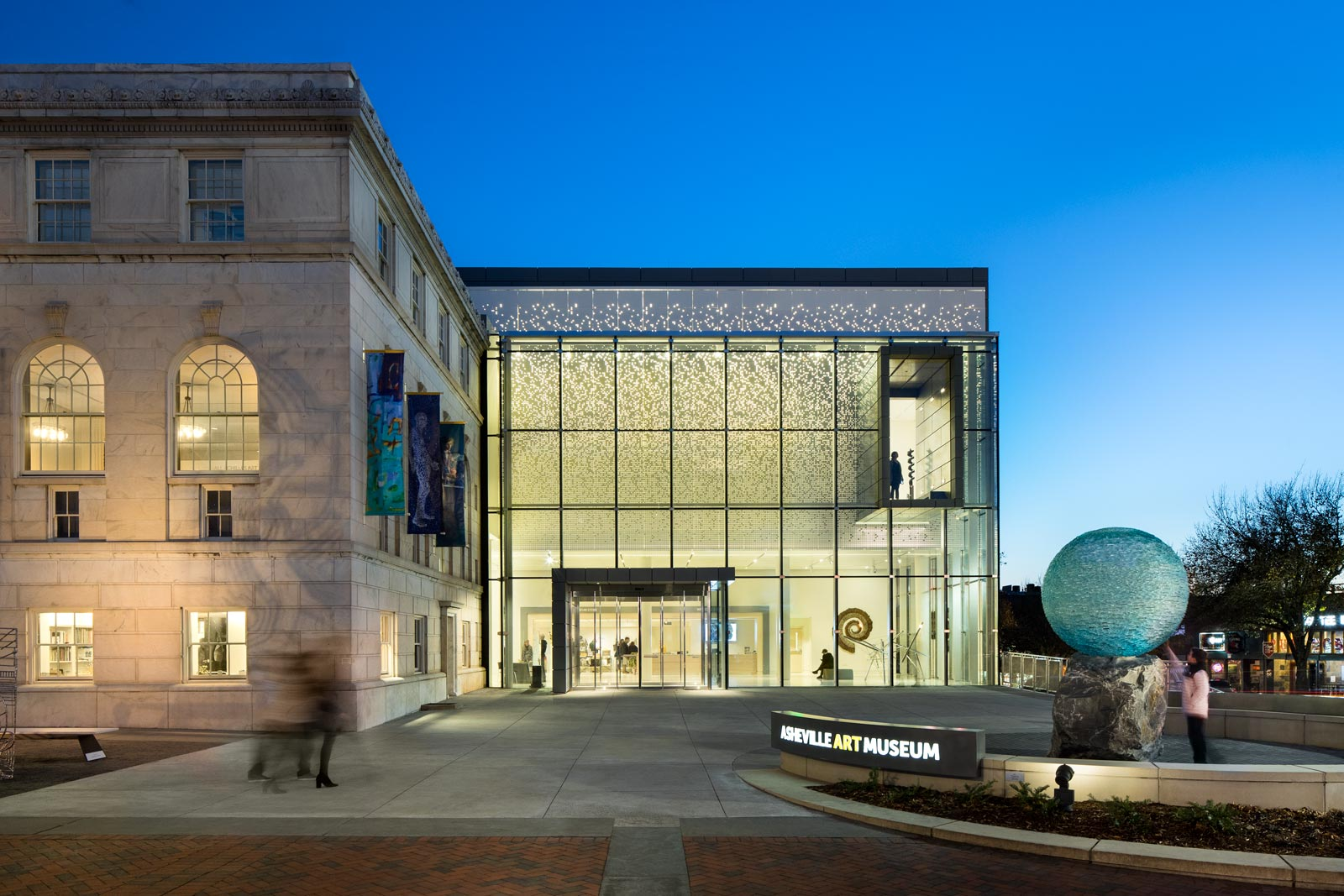 Asheville Art Museum exterior with clear blue evening sky and signs illuminated.
