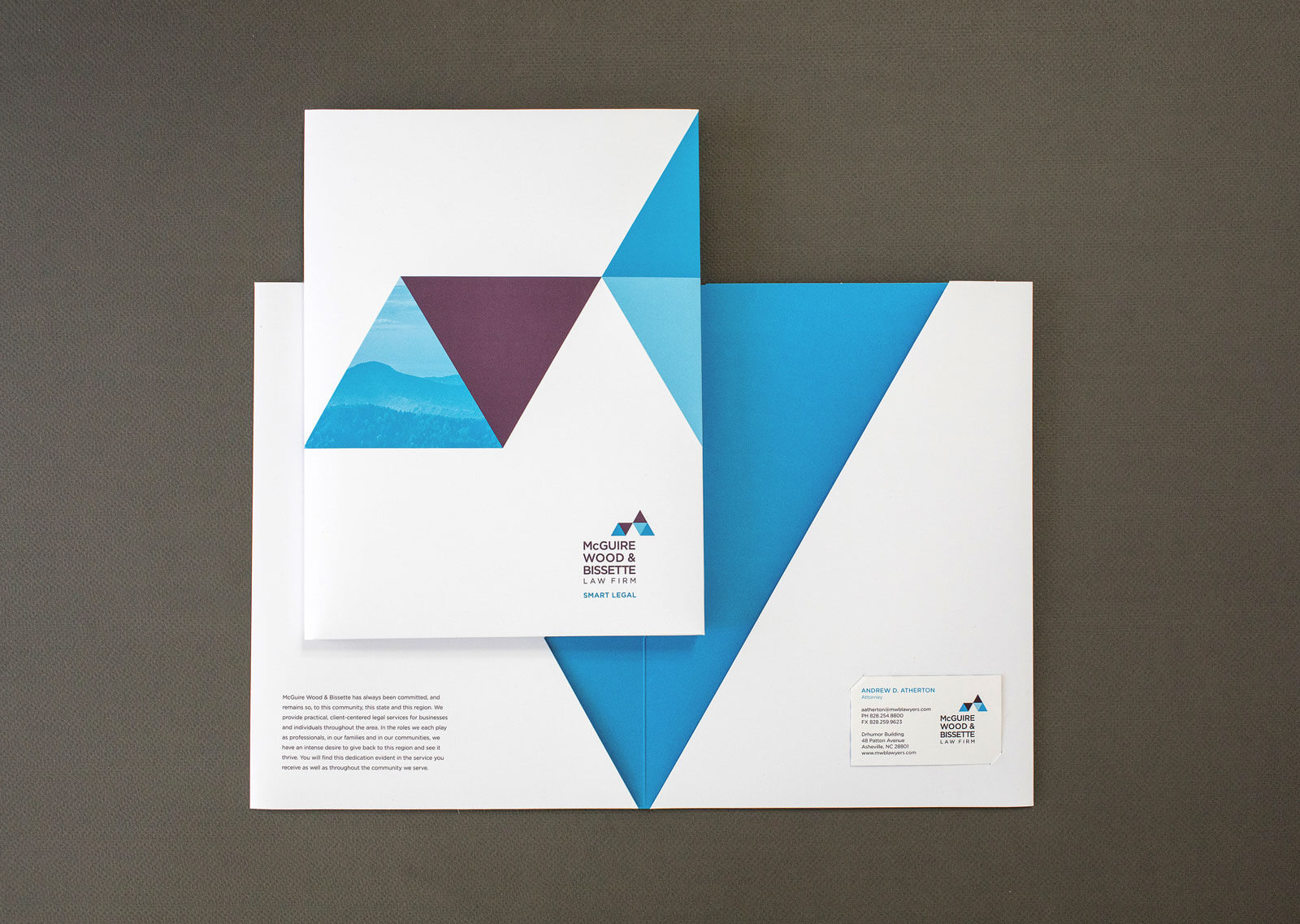 McGuire Wood & Bissette Law Firm folder cover, and opened with blue interior and letterhead and business card inserted, on a gray background.