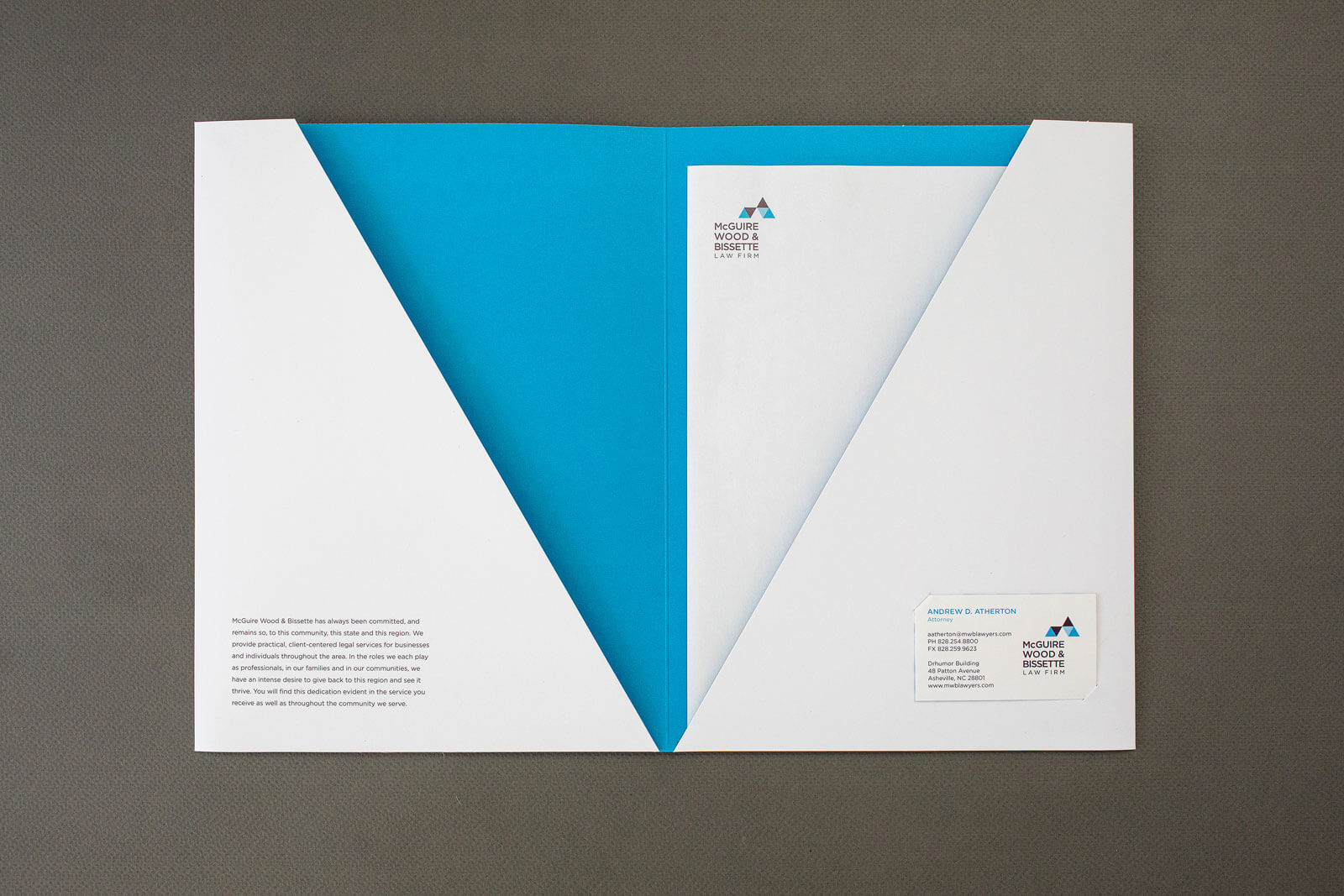 McGuire Wood & Bissette Law Firm folder, opened with blue interior and letterhead inserted, on a gray background.