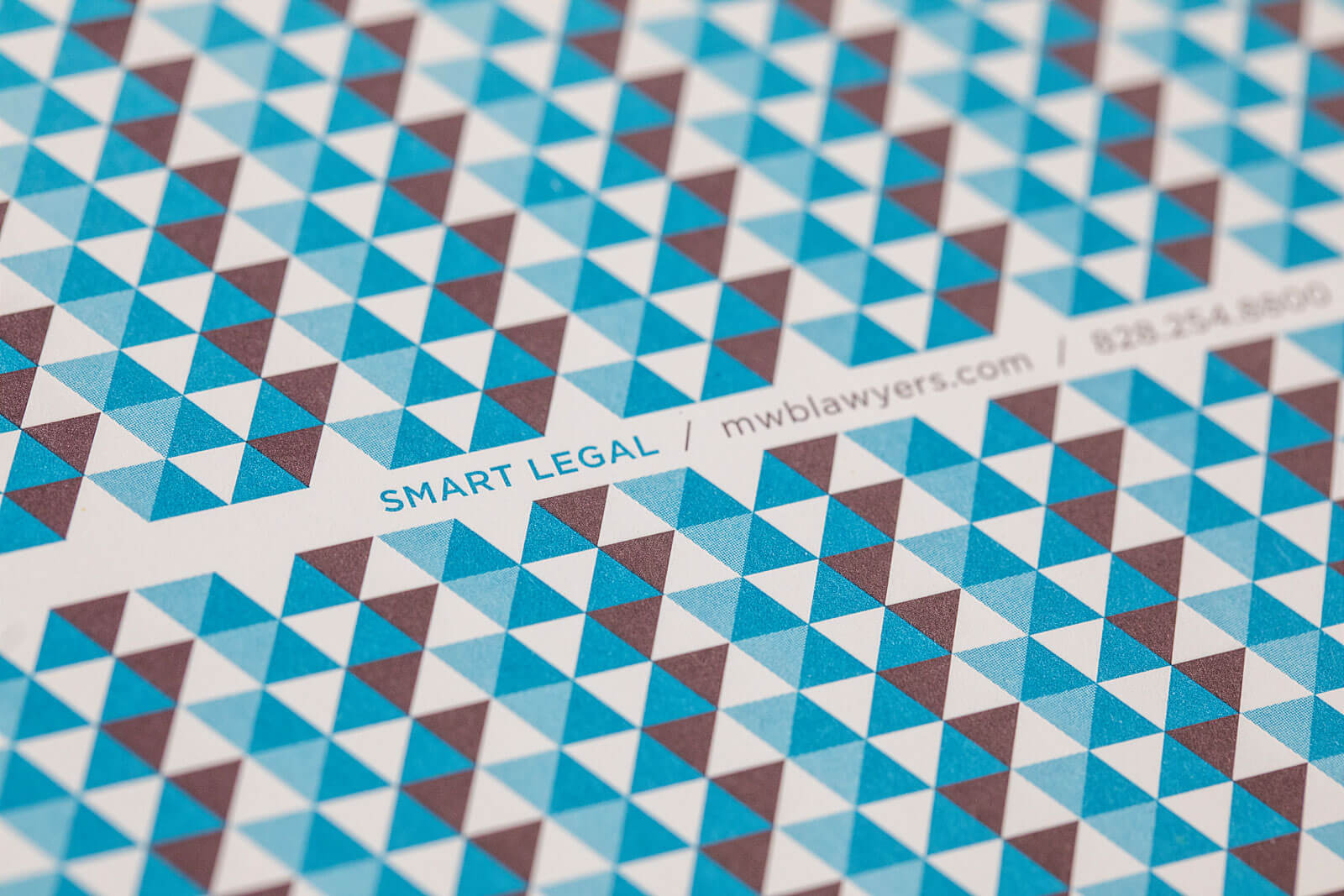 "McGuire Wood & Bissette Law Firm business card detail tightly cropped to show a blue and burgundy triangle pattern and ""Smart Legal"" tagline."
