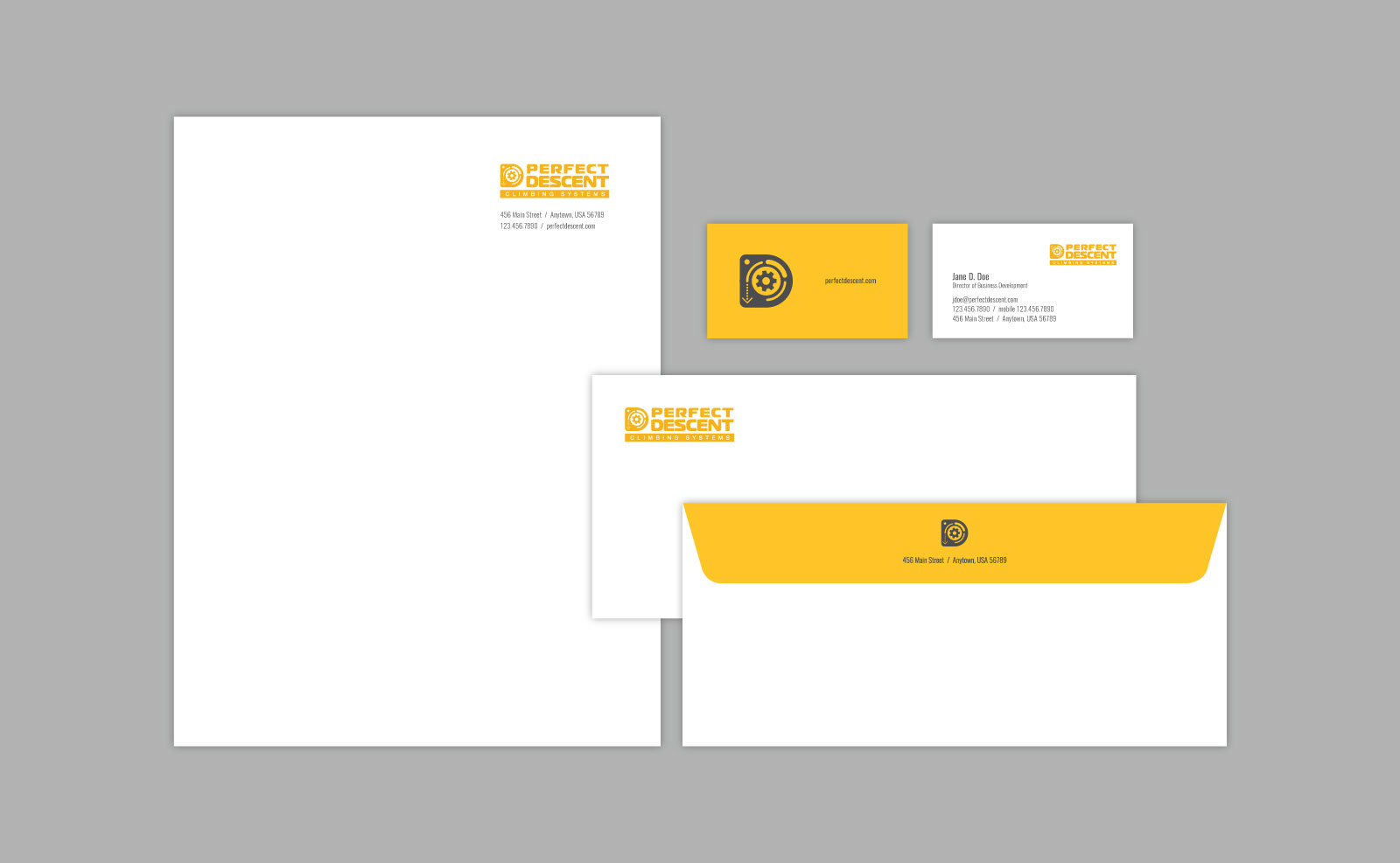 Stationery letterhead, business card, and envelope for Perfect Descent brand. Elements in white, yellow and black shown on a gray background
