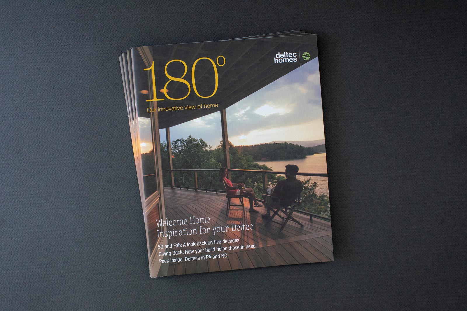 Deltec Homes 180° Magazine cover with couple sitting on a deck enjoying a sunset view of a lake