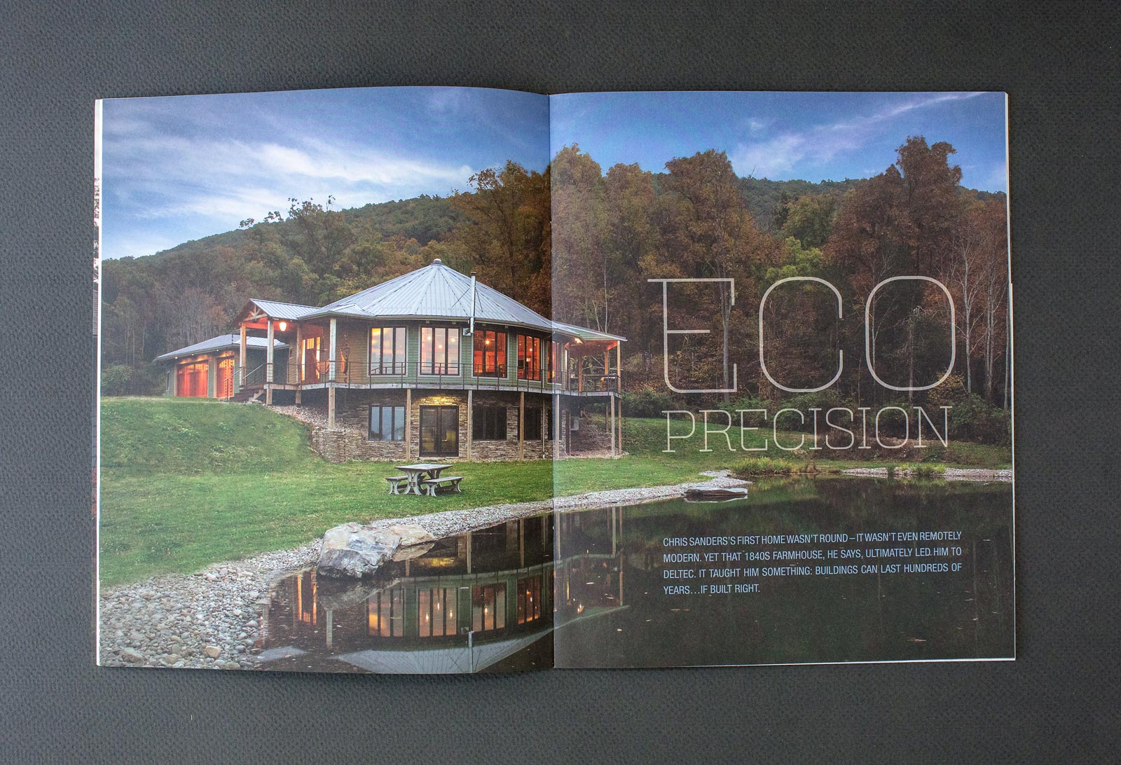 Deltec Homes 180° Magazine spread with round home, blue sky, and pond in foreground