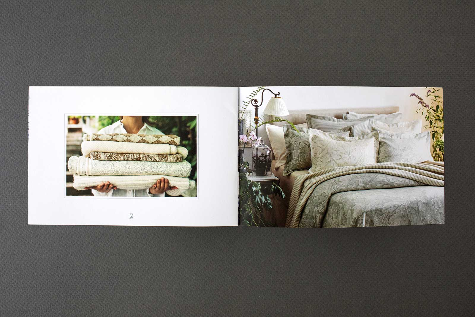Catalog spreads for The Oriole Mill, showing a bed with woven earth-tone comforter and pillows on bed. Image showing woman holding throw blankets.