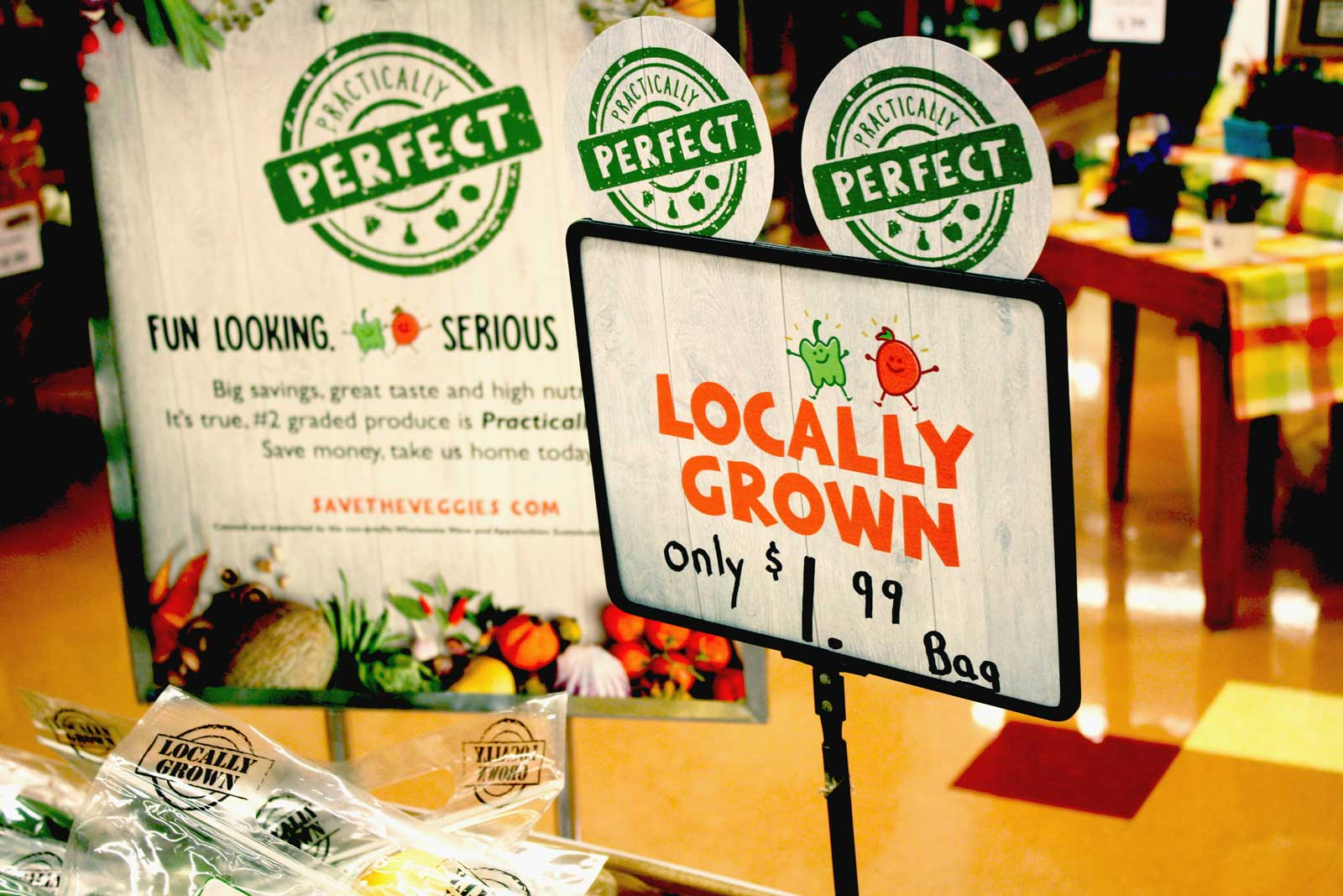 Practically Perfect brand in-store signs identifying locally grown vegetables