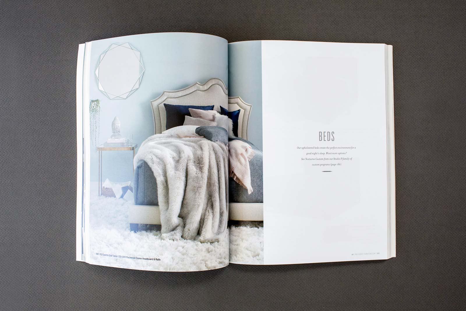 Precedent Furniture catalog spread with a bed and cover. Blue wall and a neutral blanket.