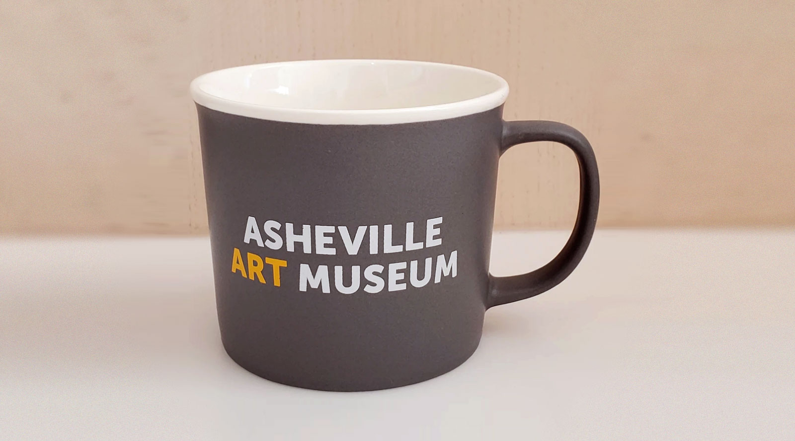 Asheville Art Museum coffee mug with white and yellow logo against a gray glaze