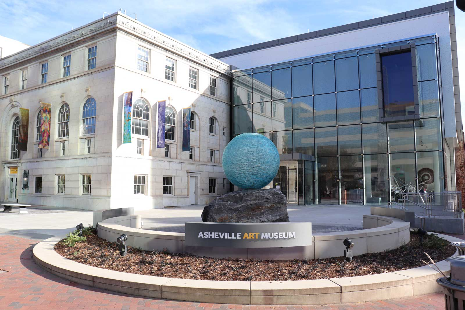 Asheville Art Museum exterior with clear blue morning sky and banner flag signs and entry sign