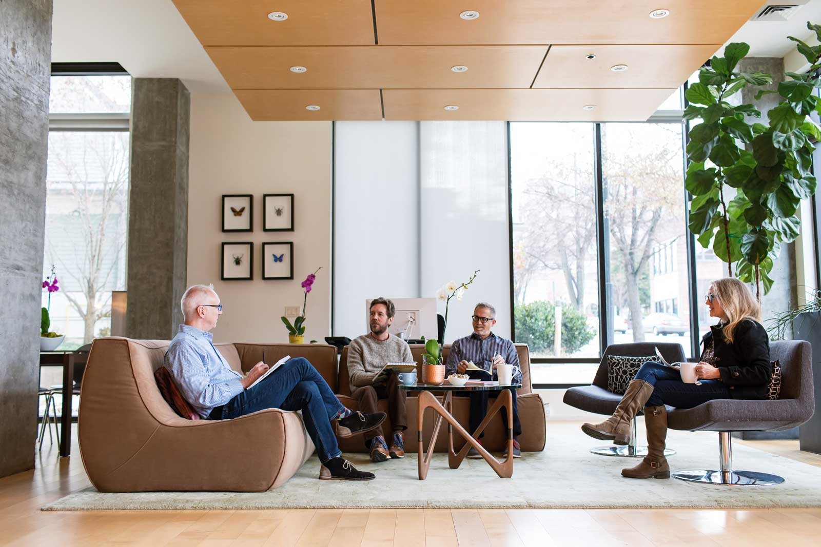 828 design office shot with Jim Chris Tom and Lainie sitting on a sectional and chairs with large windows in background