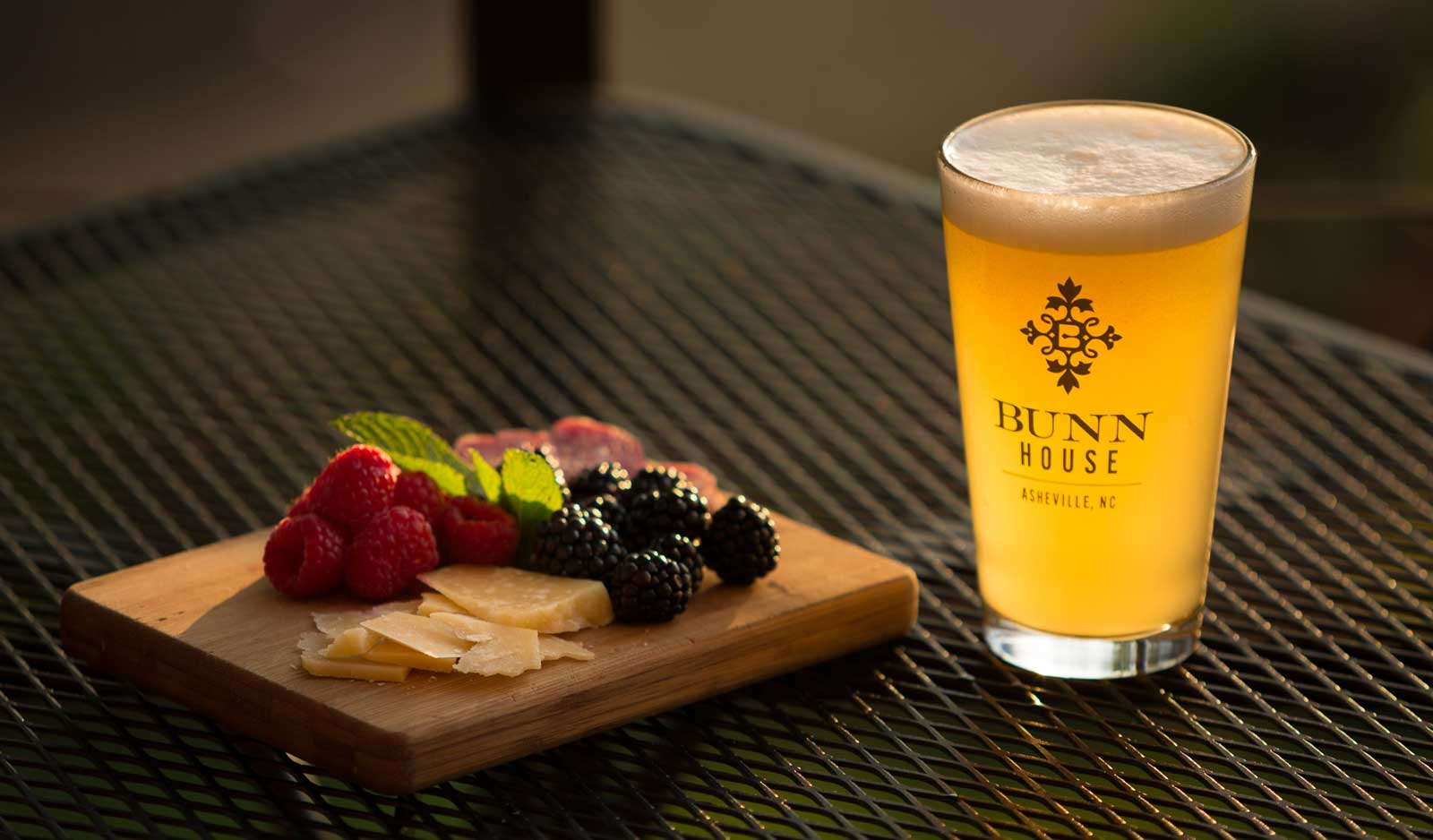 Pint glass with Bunn House Boutique hotel logo has golden beer glowing in warm light waits to be drank, and a cheese board with cheese and fruit waits to be eaten.