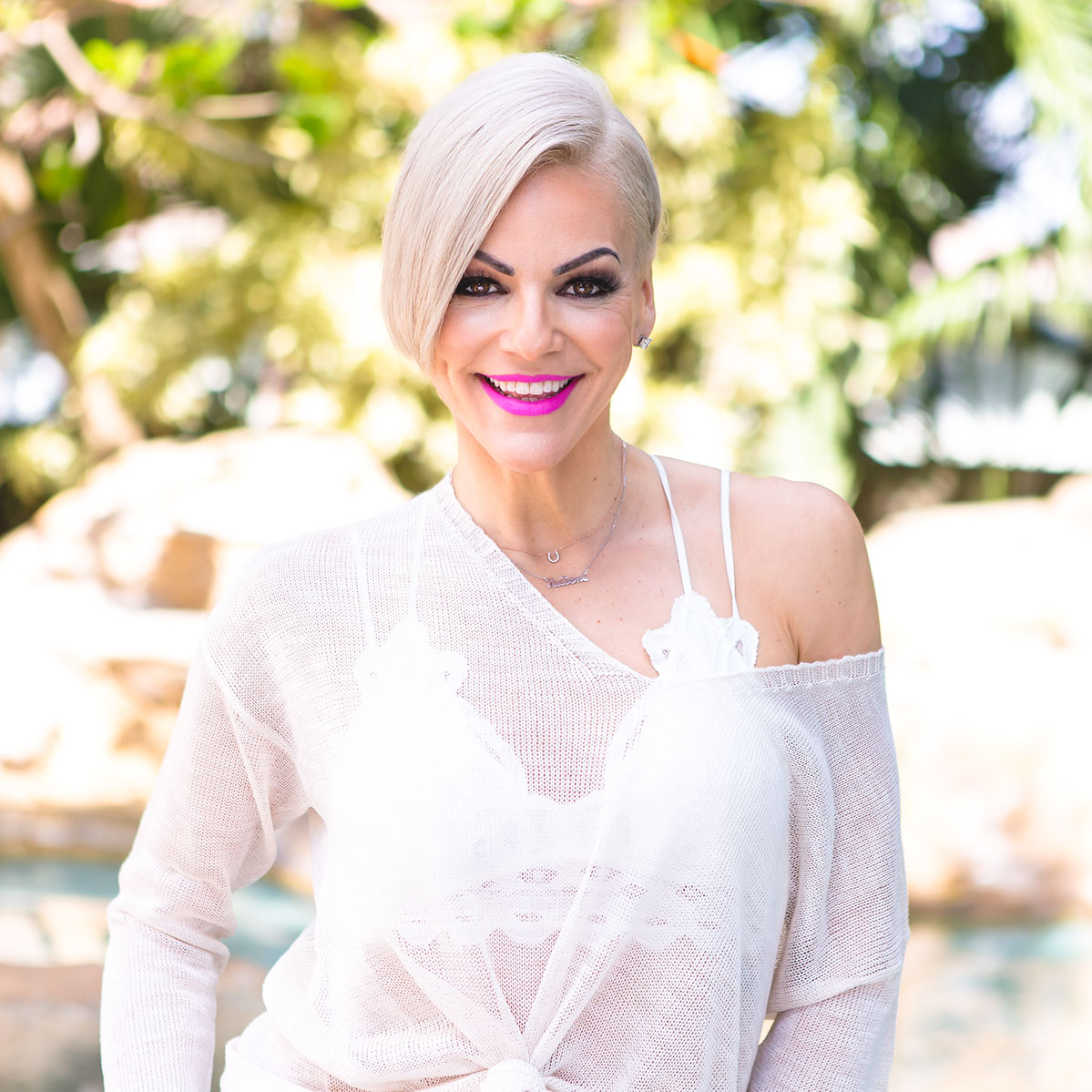 Danielle Natoni smiling with hot pink lipstick and short blond hair in front of palm trees and a pool in Miami, FL