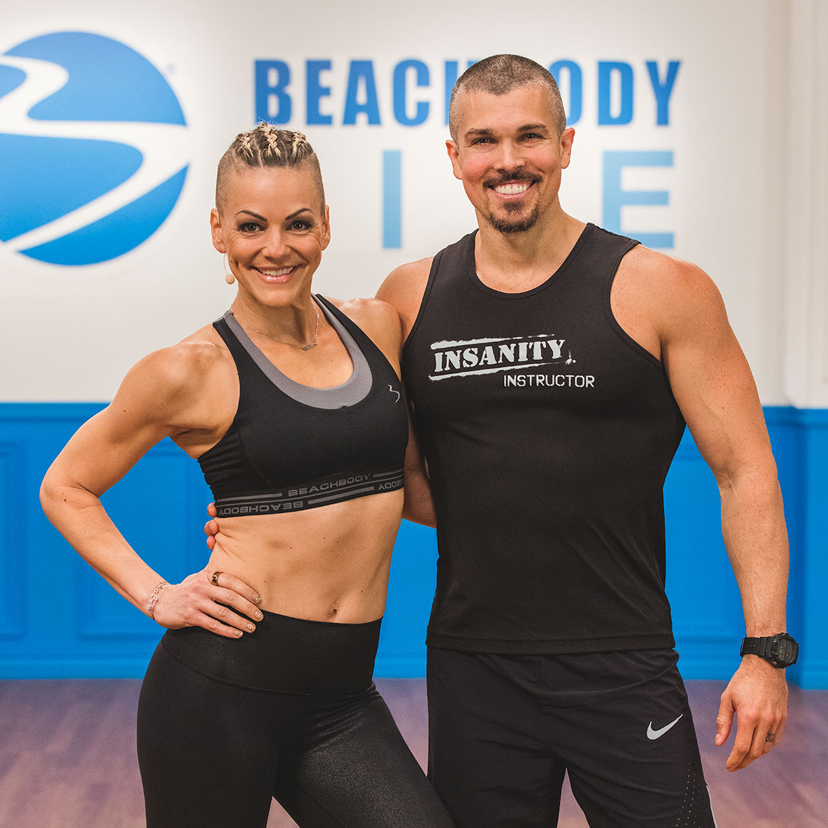 Danielle Natoni wearing a black Beachbody LIVE sports bra and tights, smiling with her hand on her hip, and standing next to her smiling husband, Darren Natoni, wearing a black INSANITY instructor tank top