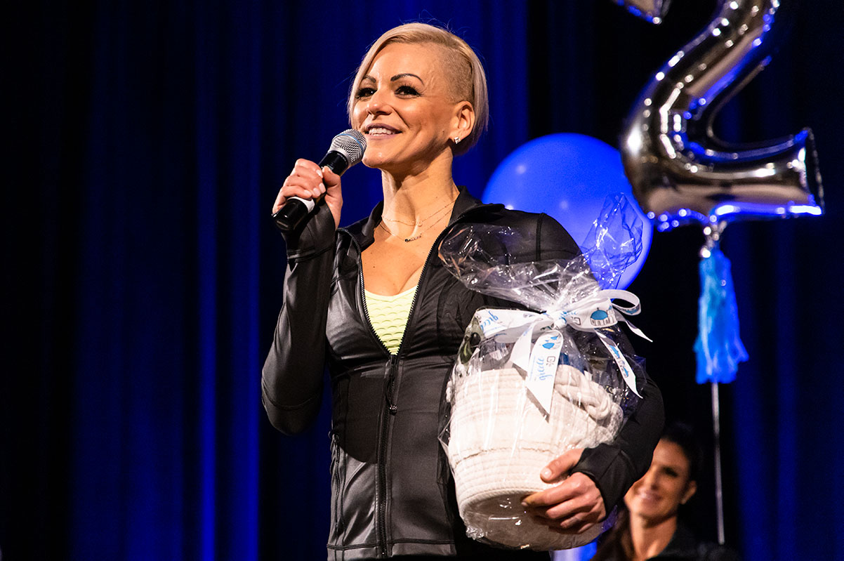 Danielle Natoni speaking on stage with a microphone while holding a gift basket awarded to her for finishing 2019 as a Top 10 Team Beachbody Coach