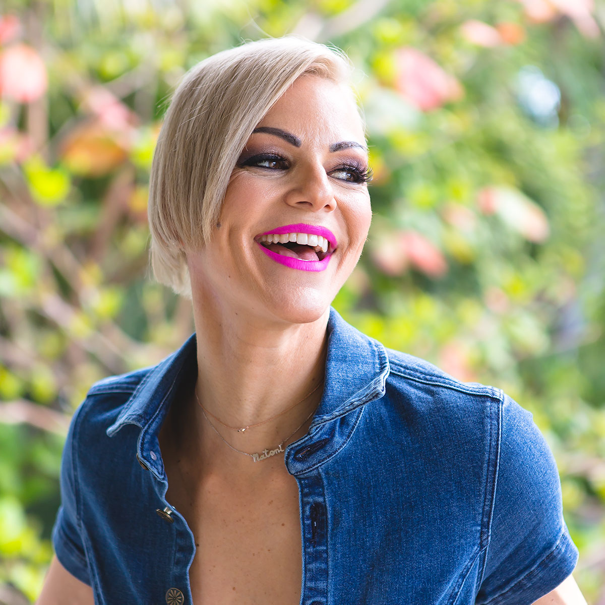 Danielle Natoni smiling with blond hair and pink lipstick