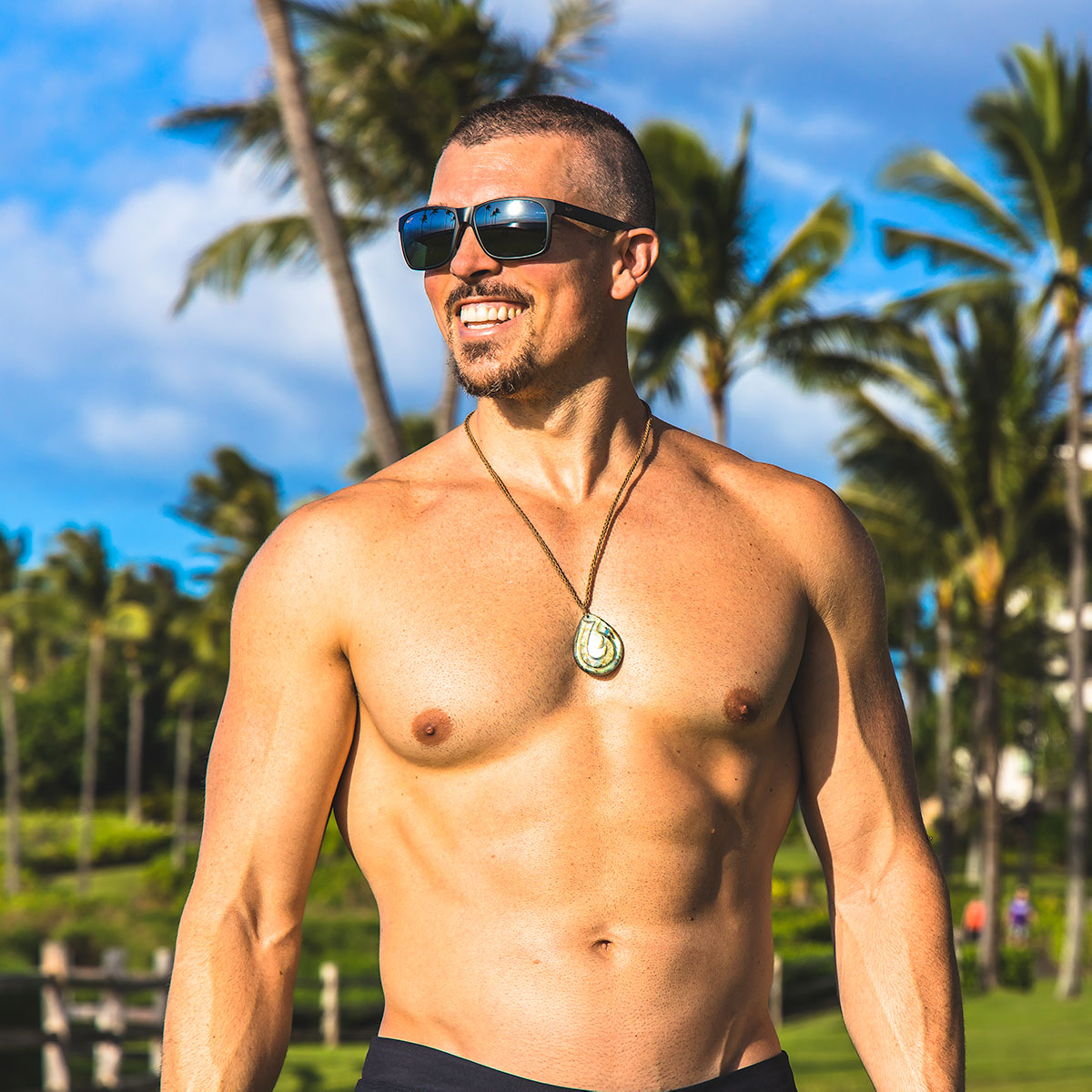 Darren Natoni standing shirtless in a tropical environment of palm trees and green grass under a blue sky while smiling and wearing black Maui Jim sunglasses and a Hawaiian fish hook pendant around his neck from Maui artist Kai Chow