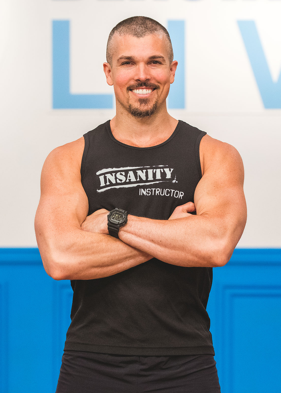 Darren Natoni standing with his arms crossed wearing an INSANITY LIVE tank top in front of a white wall with a blue Beachbody LIVE logo on it