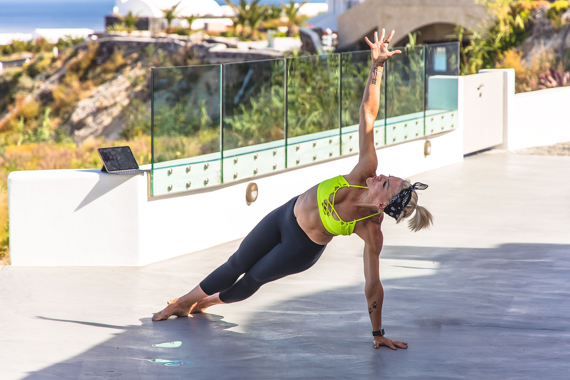 Danielle Natoni holding a side plank with one arm in the air while working out to Beachbody On Demand on her iPad while traveling in Santorini, Greece