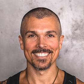 Headshot of Darren Natoni in a black tank top smiling against a concrete wall
