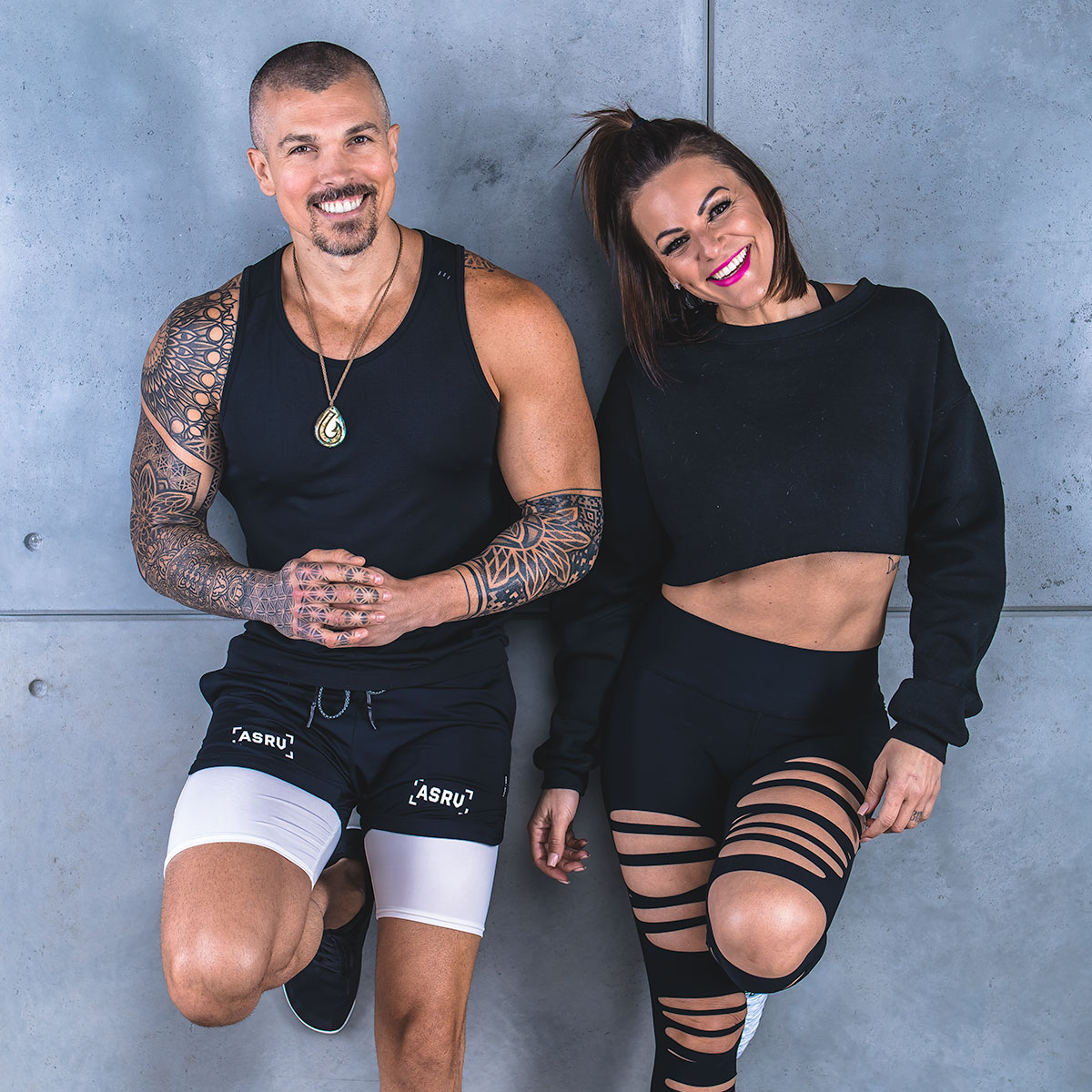 Darren Natoni (left, wearing a black tank top revealing sacred geometry tattoo sleeves) standing next to wife, Danielle Natoni (right, wearing a black crop sweatshirt and tights with slits in the thighs), each leaning against a concrete wall and smiling with one foot resting up on the wall