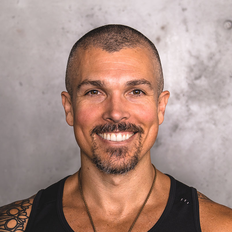 Headshot of Darren Natoni standing against a concrete wall wearing a black tank top, revealing a sacred geometry tattoo sleeve on his right arm