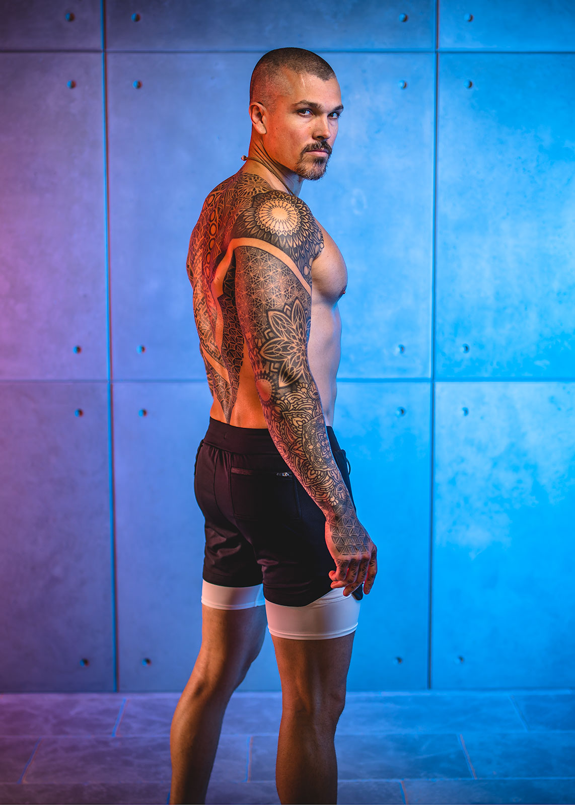 Darren Natoni standing shirtless against a concrete wall glowing with pink and blue lighting, wearing black shorts with white tights sticking out the bottom, displaying a full sacred geometry tattoo sleeve extending onto his right hand