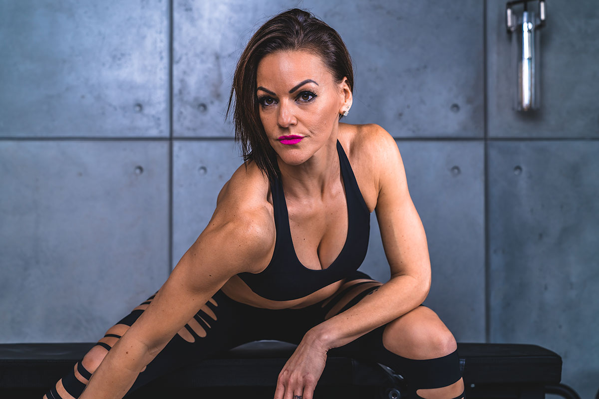 Danielle Natoni sitting against a concrete wall on a weight bench, wearing hot pink lipstick, a black sports bra and tights, and leaning over toward the camera