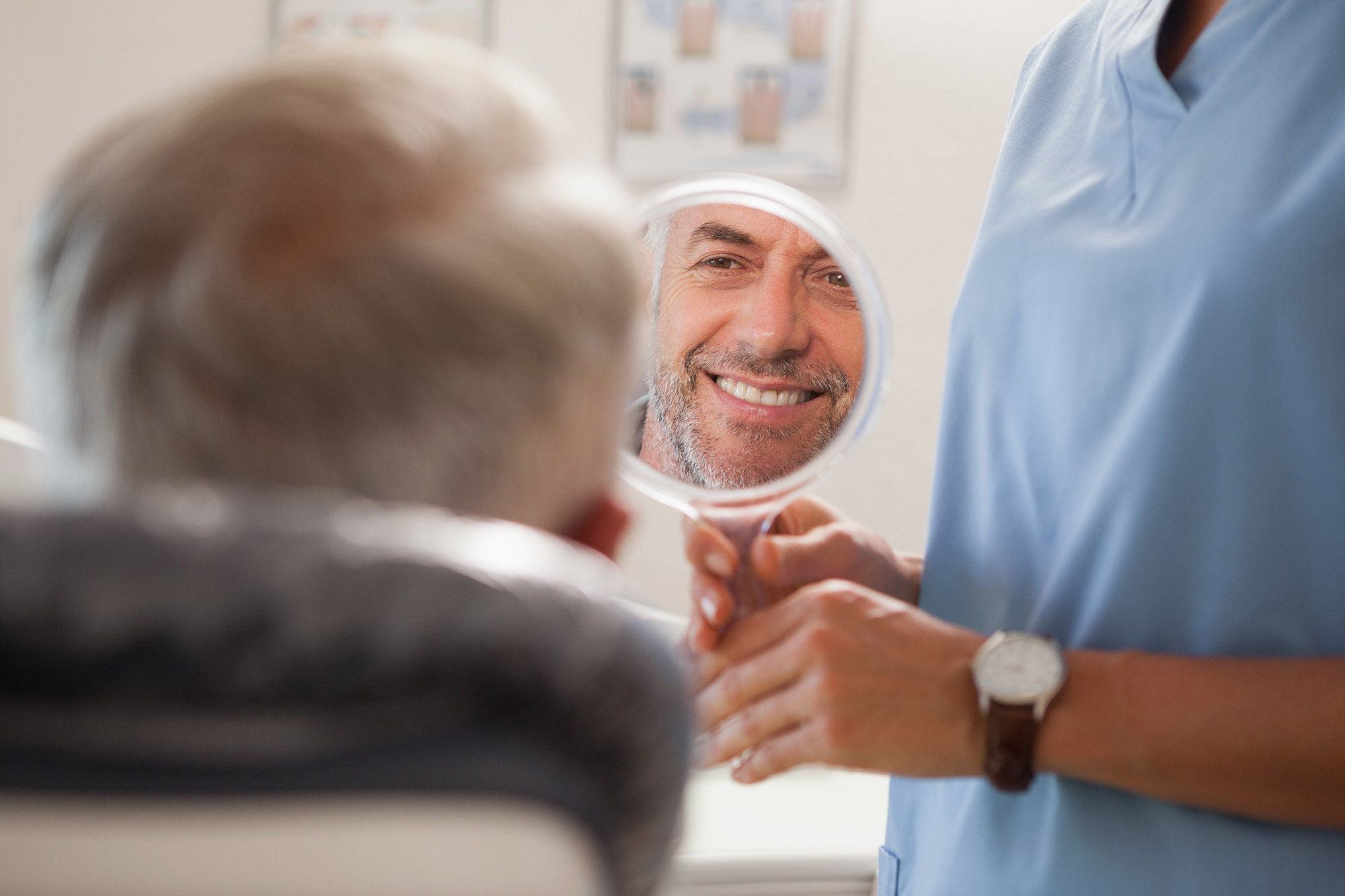 Dentist holding up mirror for patient to smile into