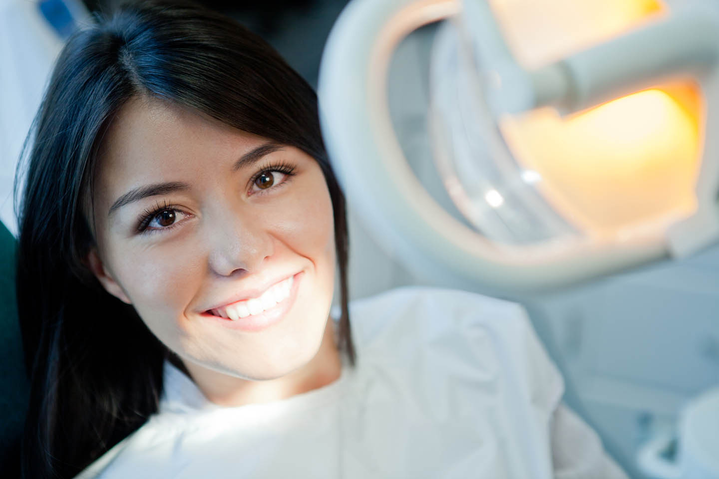 Patient smiling under a light to illuminate her teeth