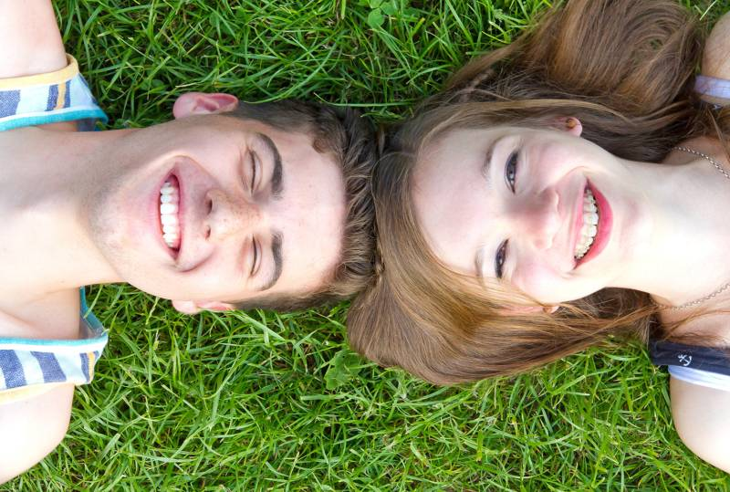 Boy and girl laying in a grass field