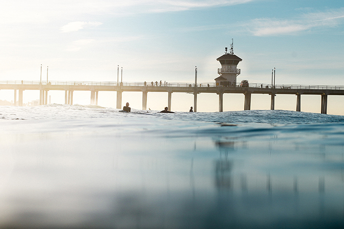 View of a pier from the ocean with surfers in the distance