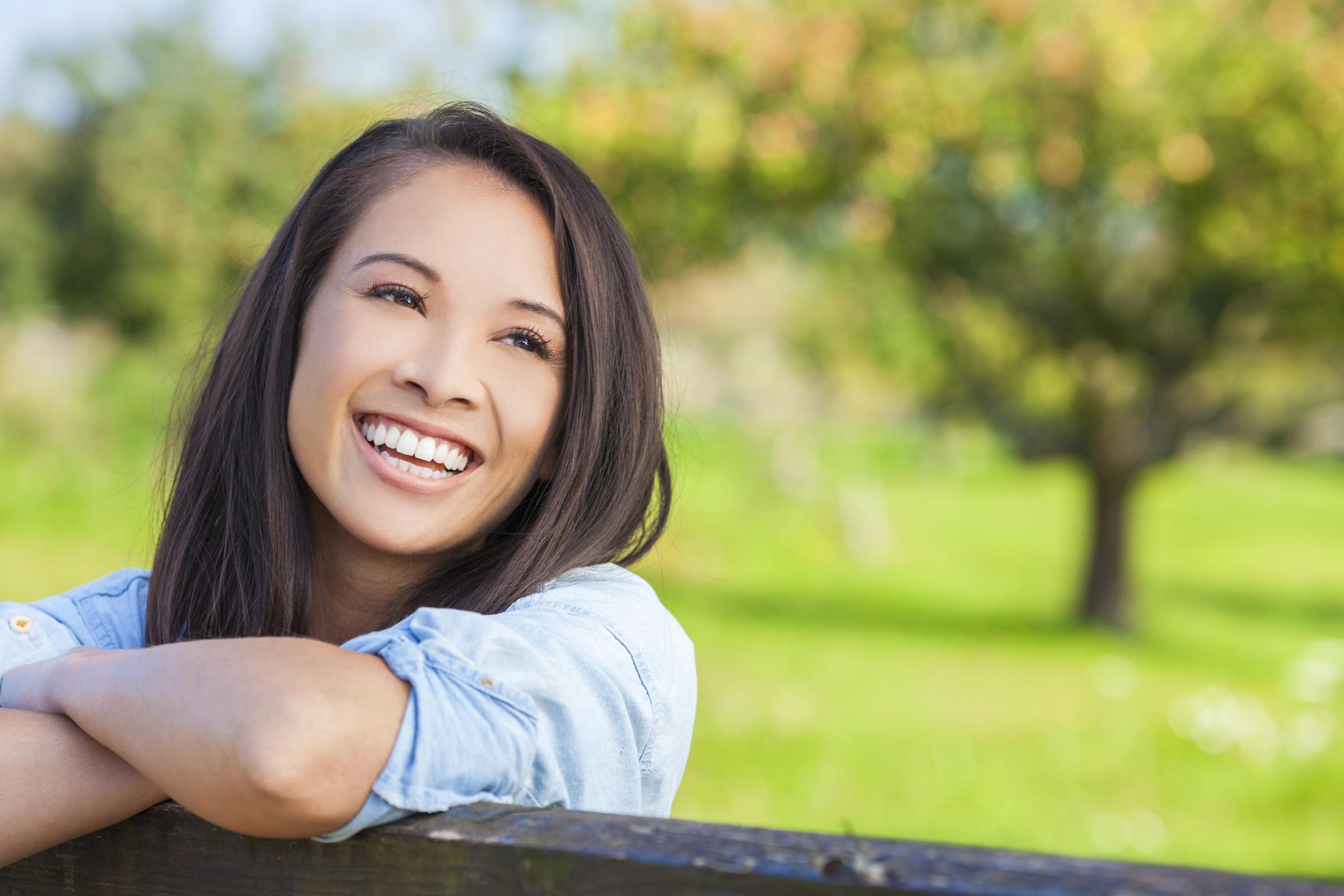 Brunette female smiling in a green field