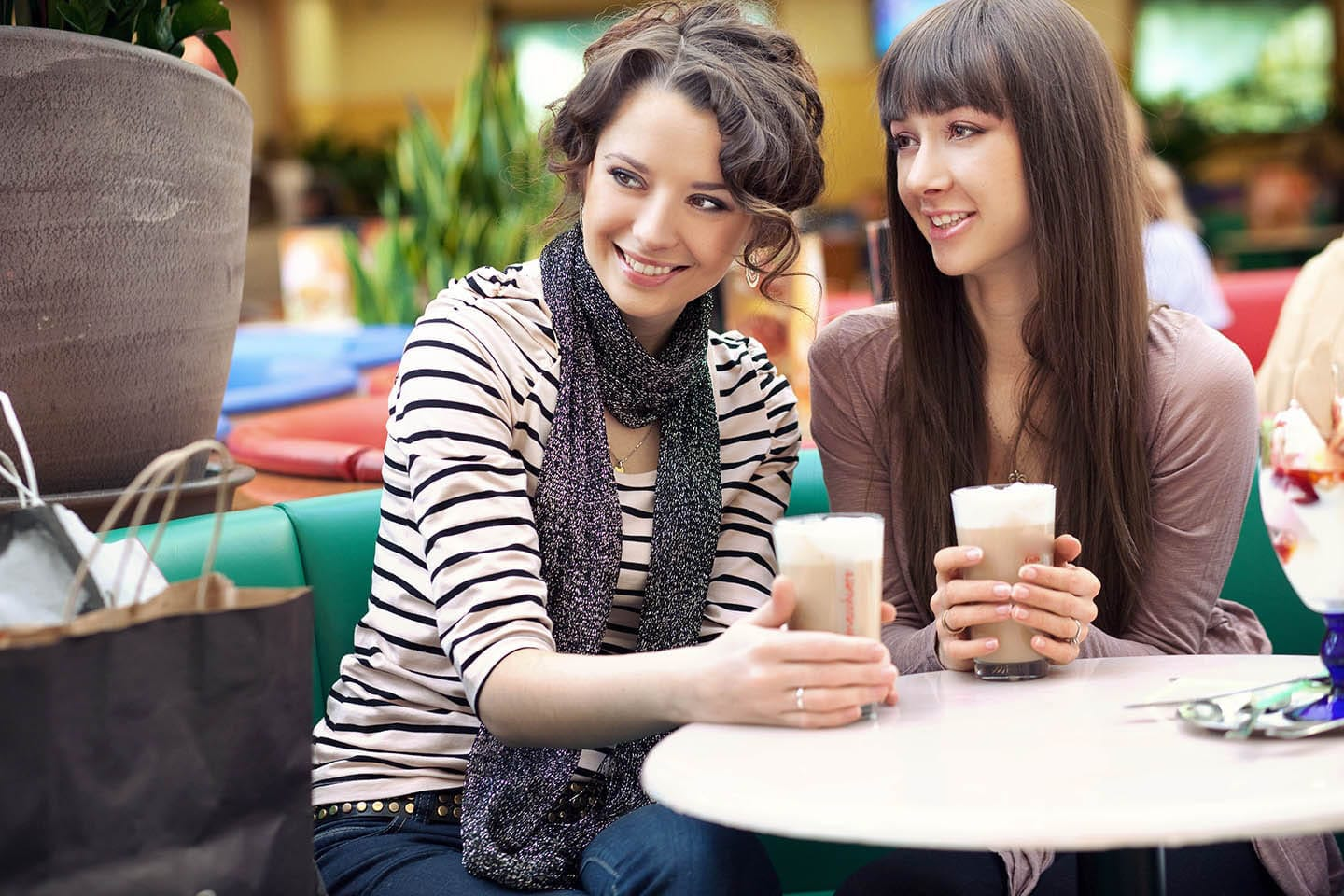 Two young females at a coffee shop smiling and talking