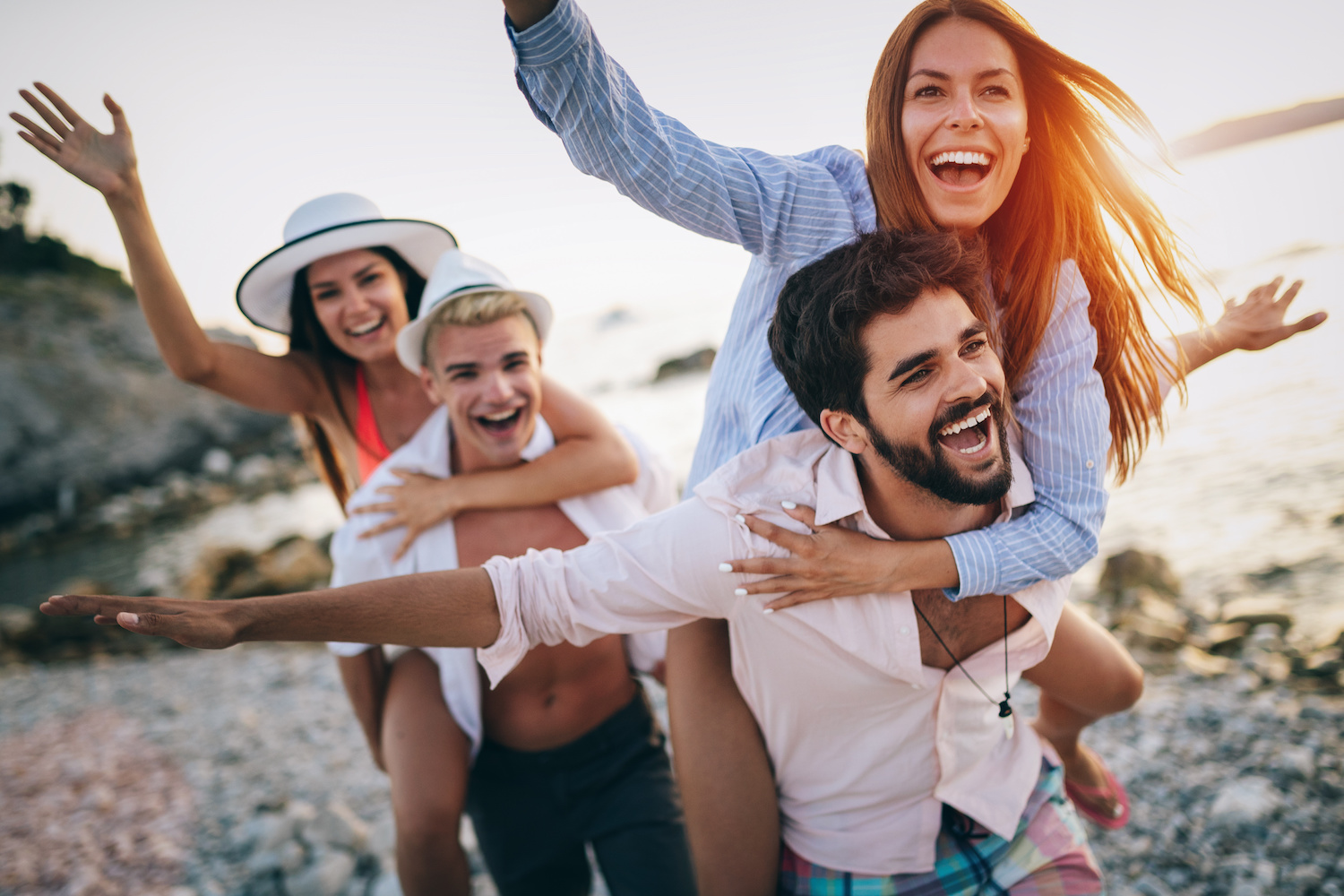 Four young people smiling and laughing while giving piggy back rides at the beach
